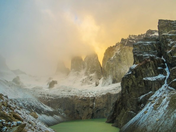 Chile - Patagonia: Early in the morning the Torres were still covered in clouds. The higher the sun rose the more clouds dissipated and the rocks finally were revealed