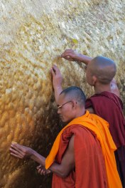 Kyaiktiyo - Two monks increasing their good karma by putting leaves of pure gold on the golden rock.