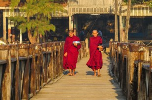 Mandalay - Two monks during the morning routine. Food they receive through begging is placed in the bowls.